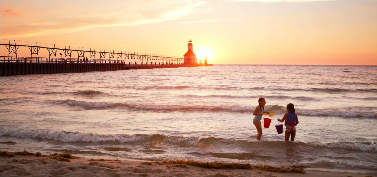 Two children play on the shores of Lake Michigan with St. Joseph Lighthouse in the background