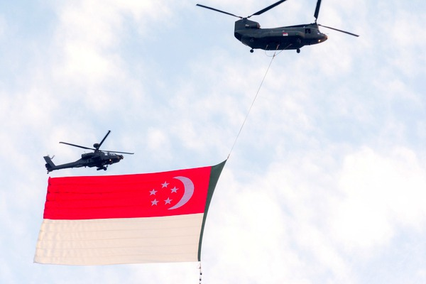 Two military planes flying a Singaporean flag
