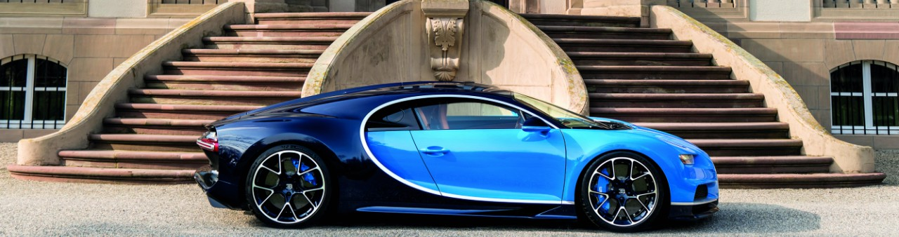 A two-tone blue Bugatti Chiron, parked in front of the entrance to a mansion
