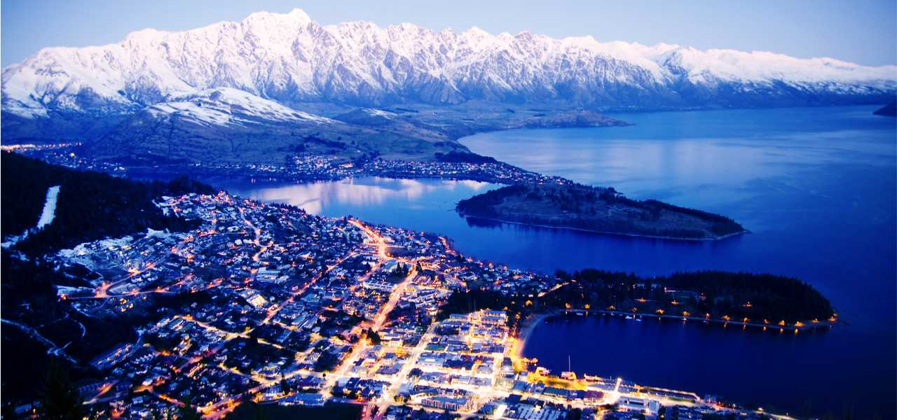 Birds Eye View of the city of Queenstown in New Zealand with snow-top mountains and Wakatipu lake in the background.