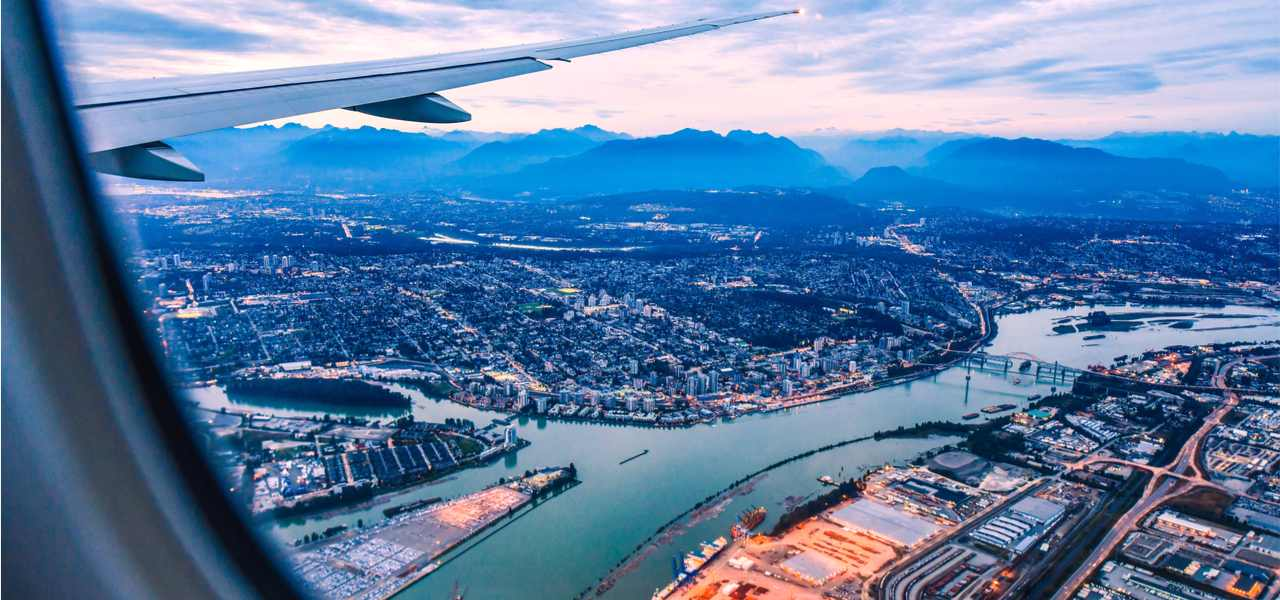 View of Vancouver from airplane window with the plane wing in the corner.