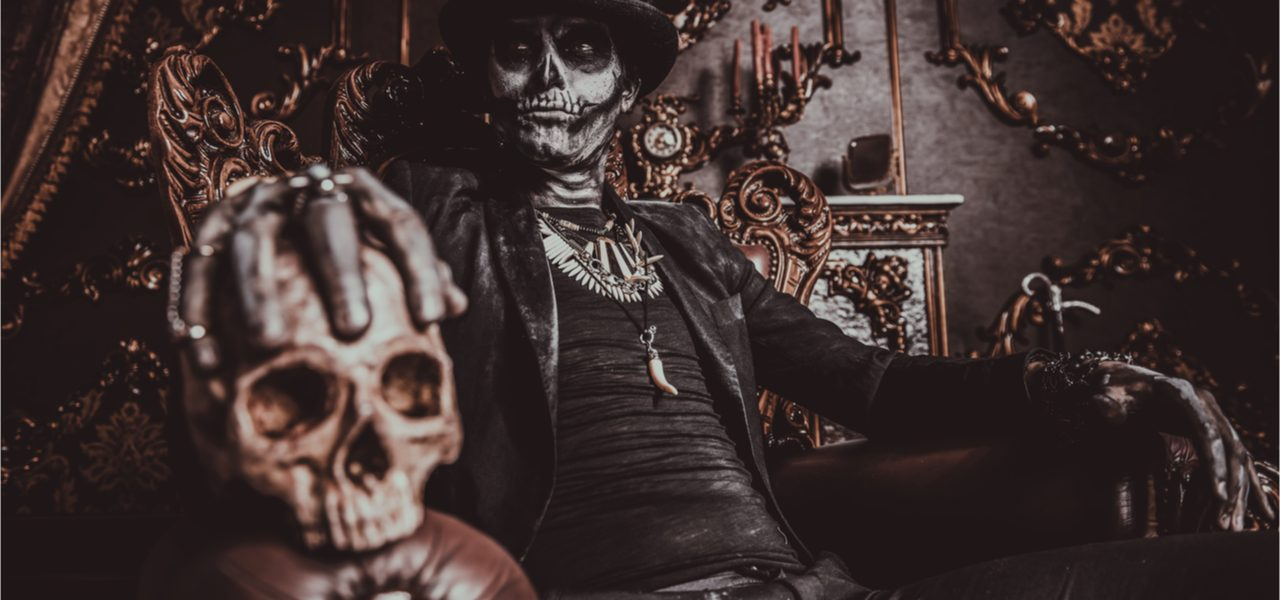 Halloween costume of a man with a skull makeup dressed in a tail-coat