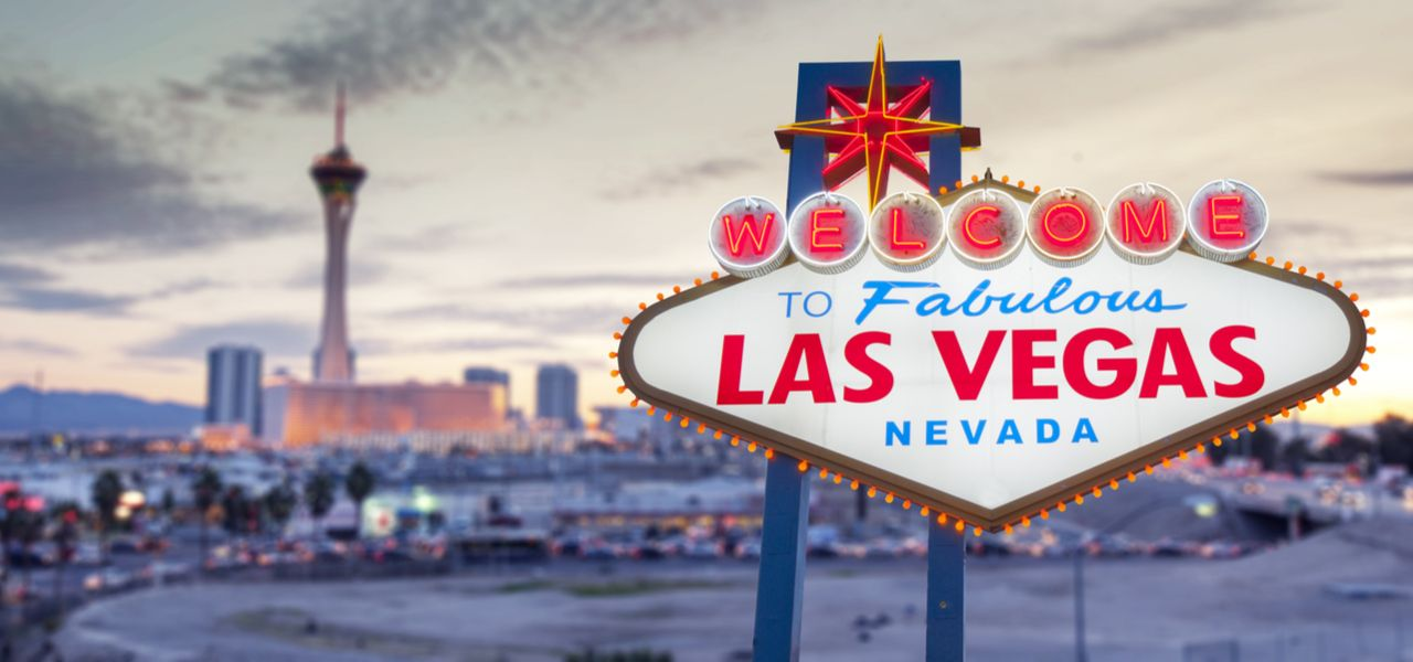 """A close-up shot of a sign reading """"Welcome to fabulous Las Vegas Nevada"""" with the city of Las Vegas in the background."""