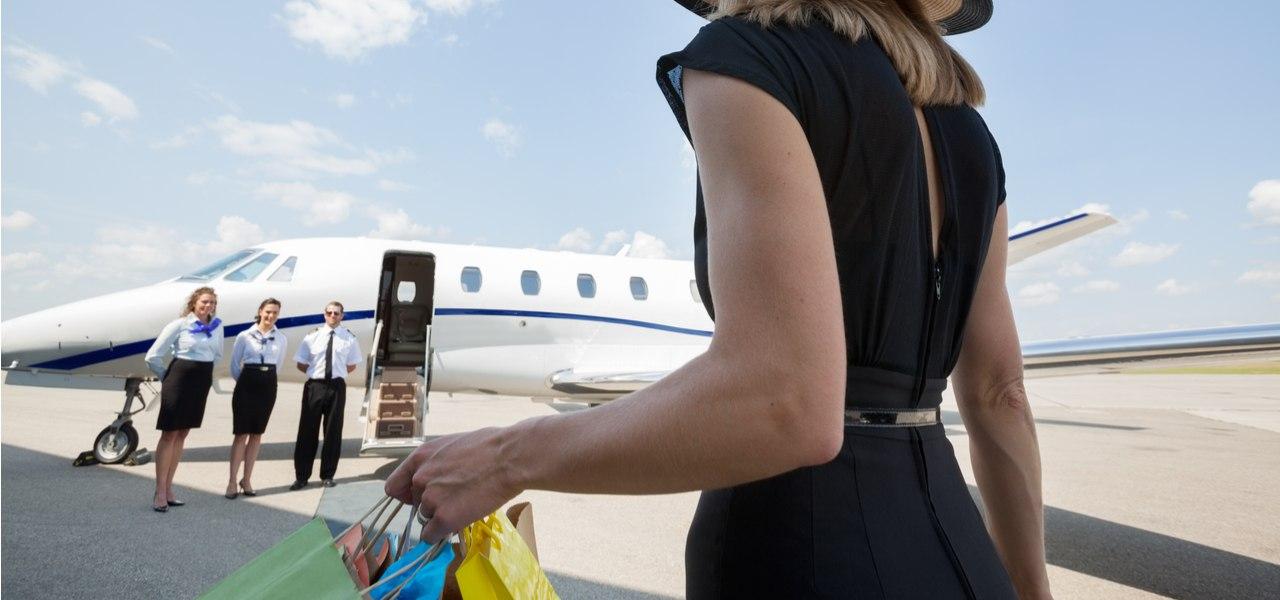 Женщина садится в частный самолет с покупками