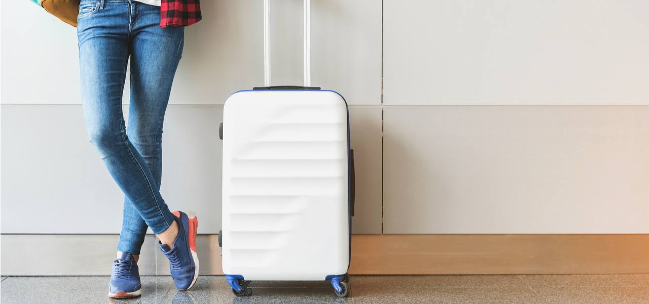 A woman in blue jeans and a red plaid shirt stands next to a white suitcase