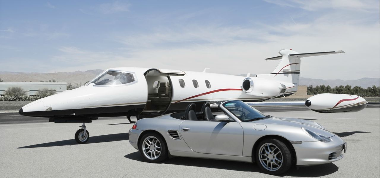 A private jet and a convertible sports car next to each other on a runway