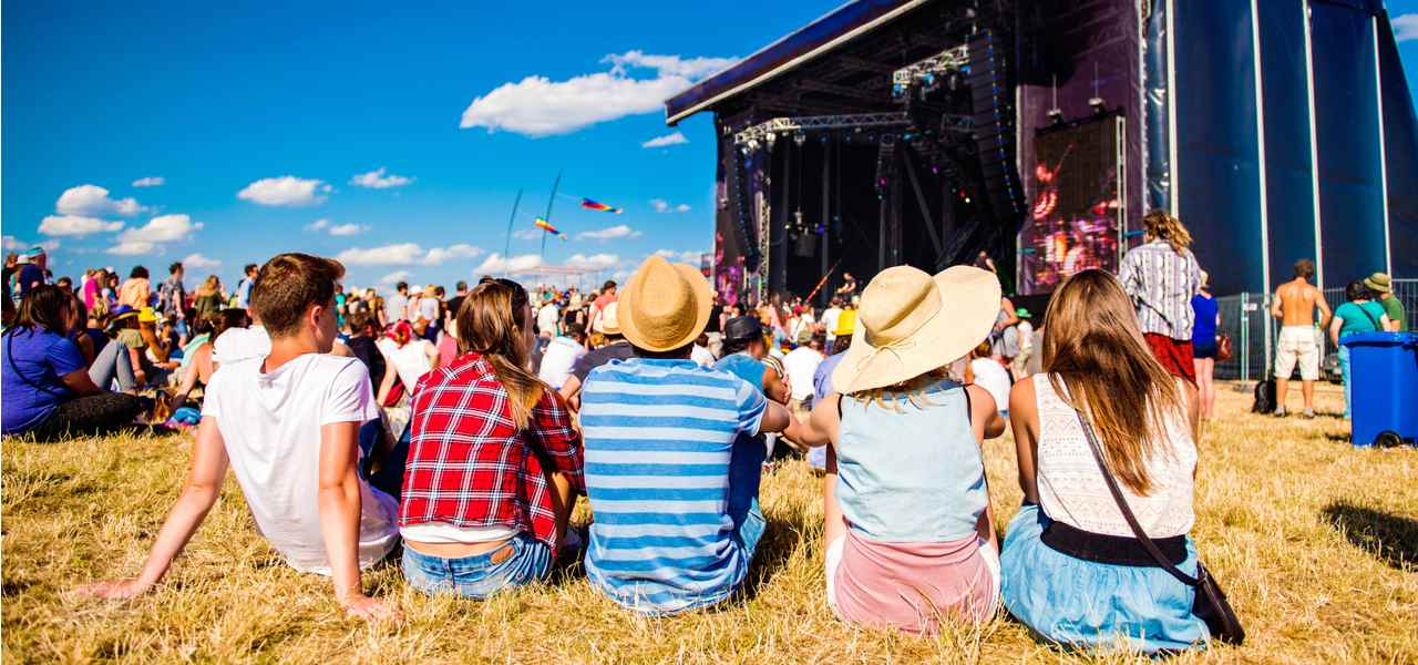 A group of young festival-goers sitting on the grass in front of a stage
