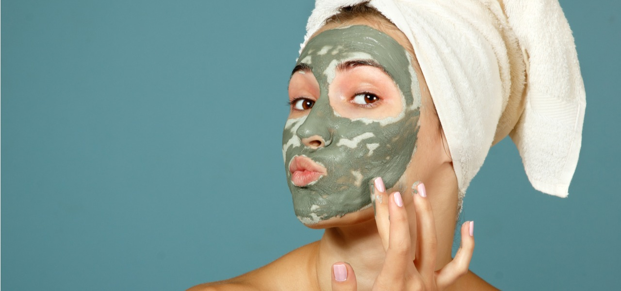 Young woman applying clay face mask