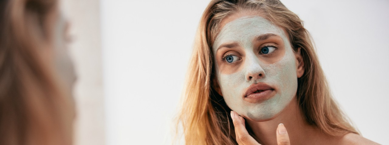 A young woman applying a green facemask in the mirror