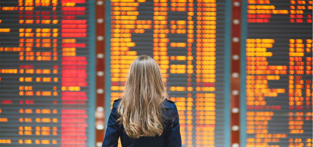 Young woman in international airport, holding passport in her hand and checking her flight on the information board.