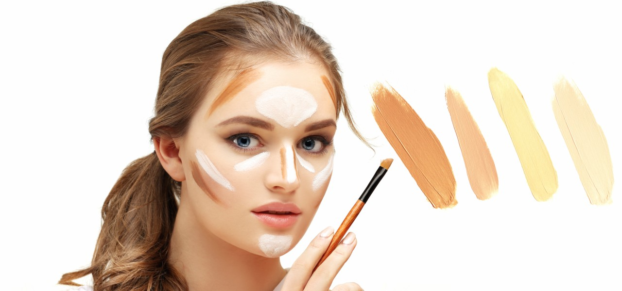 A young woman with foundation and highlighter patches holding a makeup brush