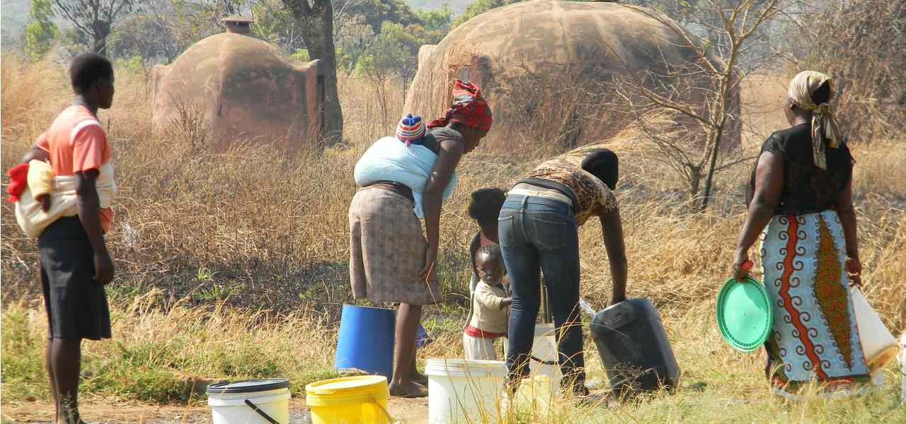 A family collects water from a single tap amidst the cholera outbreak in Zimbabwe, 2009