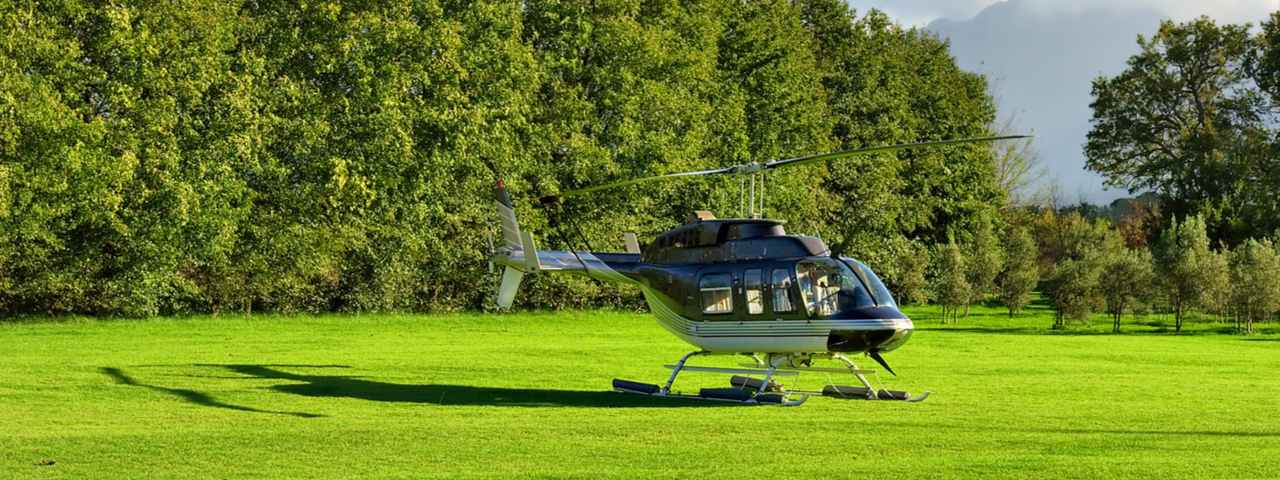 helicopter landing on a patch of green grass with trees in background